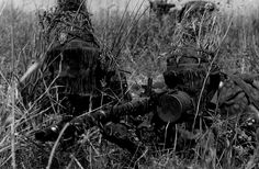 Looking like creatures from a science-fiction movie, a Totenkopf Division MG 34 team with face masks and extensive foliage tied on to their helmets during the Battle of Kursk, summer 1943.