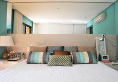 A cabeceira extensa, que ocupa toda a largura do quarto, passa a sensação de um ambiente mais amplo. O espelho acima da cama brinca com a profundidade do cômodo, favorecendo-o  Fotos Marcelo Magnani / Casa & Jardim