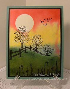 """By Naomi Witzke. Mask moon. Smear acrylic block with Strawberry Sluch, Daffodil Delight, Lost Lagoon, and Pear Pizzazz; spritz with water; stamp on watercolor panel. Lift mask. Stamp """"Winter Fenceline"""" (Serendipity Stamps) in black. Sponge more Pear Pizzazz up to hill line. Stamp grasses and birds in black."""