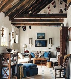 Wonderful comfortable family room with its nautical art & accessories. The heavy wood beams bring the ceiling down to a more human scale.