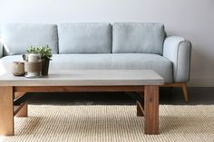 Best Designer Concrete Coffee Table - Furniture Maison  Our unique & affordable Concrete Coffee Table. The industrial look of concrete top and metal arms are paired with the warm, lightly distressed natural wood