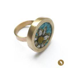 """Anillo de bronce ajustable que guarda un asombroso microbordado hecho a mano. El anillo está inspirado en la obra de Violeta Parra, específicamente en las formas representadas en las arpilleras que la artista presentó en el Louvre, en una exposición llamada """"Tapices de Violeta"""" el año 1964. Retomando el bordado como forma de expresión, Weichafe hace un homenaje a través de su joyería a Violeta Parra. Los colores utilizados, se intercalan con hebras doradas, de modo de realzar el bronce…"""