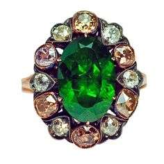 Russian 5 Ct Demantoid Fancy Colored Diamond Antique Ring. Circa 1890 with a later shank.   The ring is set with an exceedingly rare Ural demantoid garnet weighting approximately 5.18 ct, encircled by a single row of six white and six fancy colored old cut diamonds with an approximate total weight of 1.8 ct.