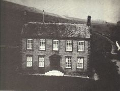 An ambrotype photograph of Haworth Parsonage taken before Patrick Bronte's death in 1861.  An ambrotype is an early type of glass negative made to appear as a positive by backing it with black varnish or paper.