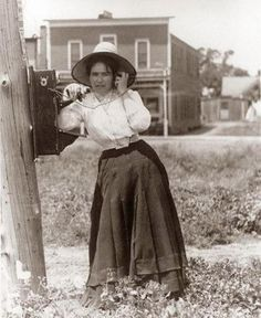 Woman talking on a hand crank oak telephone, 1900