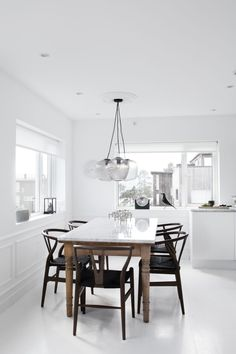 all white kitchen with a marble table and black wishbone chairs by Atelier Ribe. White Scandinavian dining room.