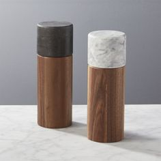 Shop 2-Piece Walnut and Marble Salt and Pepper Grinder Set of 2.   Two solid walnut cylinders topped in marble, white for salt, black for pepper.  Ceramic grinder twists left and right to adjust the fineness/coarseness.