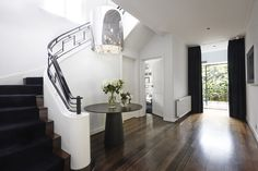 black + white entry, black stairs, black metal railing, double black doors, white walls, wood floors