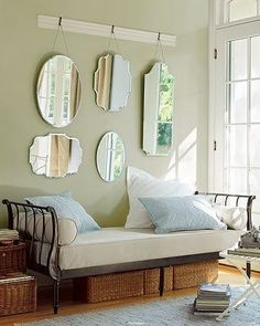 Day Bed with visible storage baskets underneath. Interesting mirror display above. Big pillows.