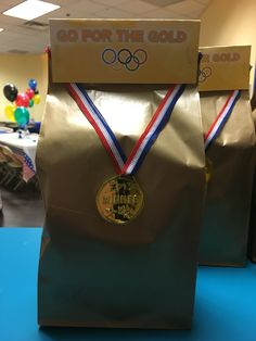 Olympics Birthday Party favor bag - gold paper bag, glue plastic medal to bag, fill with treats, print custom tags to seal bags.