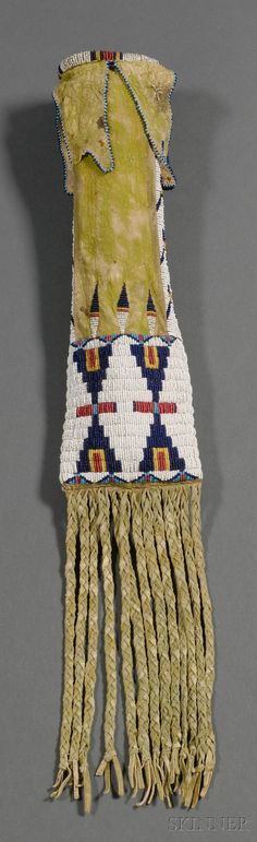 Plains Beaded Hide Pipebag, Cheyenne, c. last third 19th century, with green pigment overall, edge beaded tabs from the top, beaded with classic multicolored hourglass designs on a white background, braided fringe from the bottom, lg. 24 in.