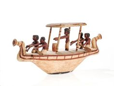 An ancient Egyptian model funeral boat with rowers.  The boat dates to the middle kingdom of Egypt (circa 2000-1700 BC) and is carved from painted wood. It features lotus flowers on the stern and prow, along with depictions of rowers and a priest.  The model is a depiction of an ancient Egyptian funeral barge.