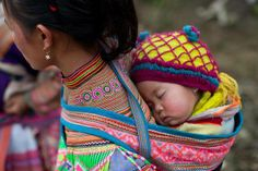 A young mother from the ethnic Flower Hmong tribe and her baby make their way to the weekly Cao Son market. In the mountains of northeastern Vietnam it is a weekly pilgrimage for many of these people