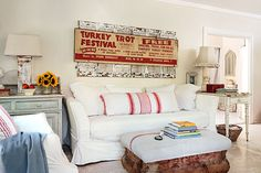 The owner of this 1920s home outfitted her cottage with a white, overstuffed sofa and chair, a large vintage festival sign attached to a frame of old shutters, and an ottoman made from an old box with vintage grain sacks used as cushion fabric.