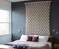 Let your wall hanging play double-duty as both a focal point in the room and a headboard. Source: Style Carrot.
