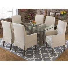 Industrial design is captured through a sandblasted trestle base accented with a glass top for a light and airy feel. Upholstered arm chairs in a casual linen fabric create a balanced and stylish look. Set includes table and four upholstered arm chairs.