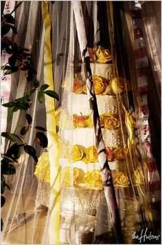 White with yellow roses in a tent of ribbons - Photo by Jason