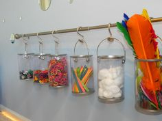 From Play At Home Mom: Close up of paint cans in art center. Curtain rod from Home Depot, shower curtain hangers as hooks also from Home Depot, and buckets from Michaels.