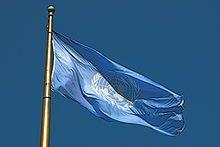 20. Okt. 1947: Die Vereinten Nationen erhalten ihre noch heute gültige Flagge. Die Flagge zeigt auf einem himmelblauen Flaggentuch in weiß die Erdkugel umrahmt von zwei Olivenzweigen. Die Karte zeigt die von Menschen bewohnte Landmasse. Im Mittelpunkt liegt der geographische Nordpol, um ihn die Kontinente der Nordhalbkugel, die Südhalbkugel ist durch die Projektion, welche einer Azimutalprojektion ähnelt, verzerrt und zu groß dargestellt.  Die Olivenzweige sind ein klassisches…