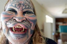 """Dennis Avner, AKA """"Human Tiger"""" has had multiple body modifications including splitting of his upper lip, surgical pointing of the ears, cheek and forehead implants, tooth filing, tattooed stripes, contacts with split irises, and facial piercing - to which whiskers can be attached!"""