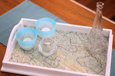 Spray paint an old wooden tray and line it with an old map!