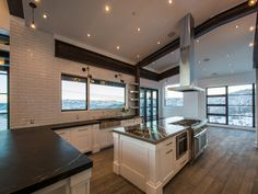 Beautiful kitchen features a sloped ceiling accented with stained wood beams stand over a kitchen peninsula fitted with a soapstone countertop under a white glazed tiled backsplash.
