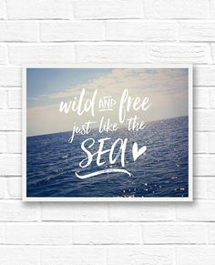 """A fun quote print that reads, """"Wild and free just like the sea,"""" over a photograph of the sparkling blue ocean. Inspirational feel good wall art."""