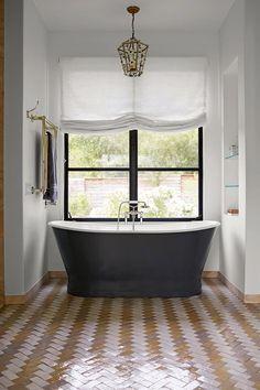 A bathroom with herringbone tiled floor, pendant light, free standing bath tub and wall mounted towel rail.