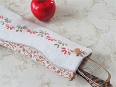 This fabric epi case is hand made from a vintage embroidered recycled linen. Soft tones of peach and coffee are stitched carefully into the vintage linen, which edges one side of the pouch. Peach print fabric. Lightly padded, and comes with a loop closure; never a zipper to jam. A small vintage glass button helps keep the elastic loop closed.   A customer bought one of these and loves it. You can also use it for a pair of small eyeglasses. If you are one of those people who likes old…
