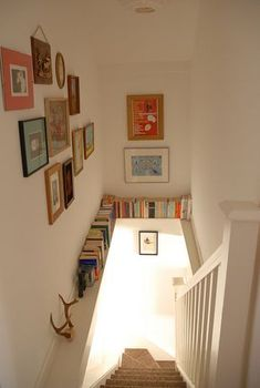 Stairwell bookcase and mismatched photos/French prints on all the walls More