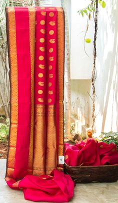PINK IRIDESCENT RED KANCHIVARAM SILK IS INTRICATELY WOVEN WITH GOLD ZARI BHUTAS. THE DETAILED GOLD ZARI BORDER AND PALLUGIVING THE SAREE DELICATE FINISH.