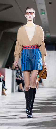 LOEWE Autumn Winter 15 look 29. Pleated cardigan-wool-beige / Skin turtle neck sweater-wool-almond / Cyborg mini skirt-suede-nappa blue -black / Filipa sunglasses-acetate-havana-transparent / Ibiza earring-silver-rhodium /  Small leaf earring-silver-black / Small leaf earring-silver-gold / Barcelona shoulder 24 bag-ostrich-suede tan / L circle belt t-calf primary red / Column ring ankle boot-calf-goatskin-black-multicolor /