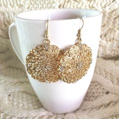 NWOT Gold Lace Dangle Earrings with Rhinestones NEW WITHOUT TAGS. Received as gift // Gold Lace Dangle Earrings with Rhinestones // Beautifully detailed round earrings. White rhinestones on edges. One center stone is missing, but is barely noticeable (as shown in photo). Jewelry Earrings