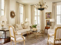 A bold neoclassical chandelier and leopard print rug anchor the pale palette of the living room, where paintings from the homeowner's art collection command attention. // Atlanta, GA