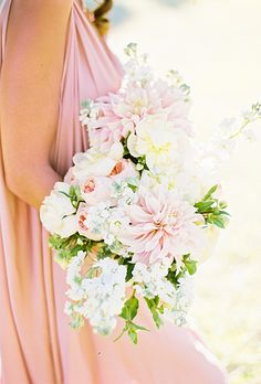 Brides.com: . A pastel bouquet comprised of dahlias, roses, and wildflowers, arranged by Sofia of Branco Prata Studios.