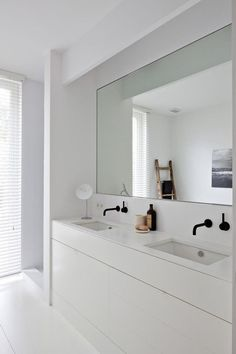 bathroom renovation // crisp, white, modern sink cabinets and black bathroom fixtures