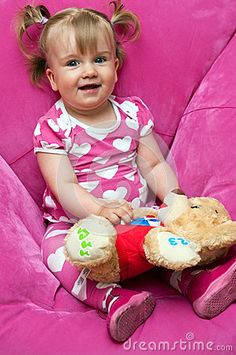 Smiling cute baby girl in pink, sitting in a puffy armchair with her teddy bear toy.