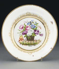 A Swansea plate from the Burdett-Couts service CIRCA 1815 Painted with a basket of luxuriant garden flowers within an elaborate gilt-scroll foliage and seed-pattern cartouche, the border painted with two moths and an insect, within gilt dentil rims 9¼ in. (23.5 cm.) diam.