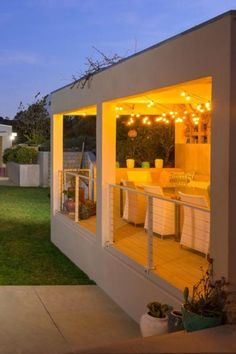 This lovely raised patio sits next to this California home's infinity swimming pool. The covered patio is decorated with lovely fairy lights and furnished with dining room furniture. It has railings on the side. #RaisedPatio #PatioIdeas #PatioDecoratingIdeas  Courtesy of Toptenrealestatedeals.com