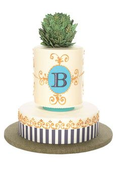 Whimsical topiary wedding cake with monogram, gold scrollwork, and black and white stripes.