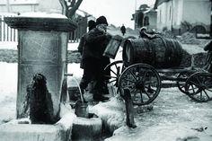 Ultimii sacagii, incarcand apa potabila si purtand-o in sacale pe strazile bucurestene. In 1929, cand Nicolae Ionescu a realizat aceasta fotografie, tagma sacagiilor era deja pe cale de disparitie, in fata modernizarii capitalei si a introducerii apei curente.