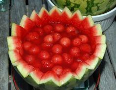 Für die Melonenbowle die Wassermelone halbieren und den Rand der einen Hälfte gezackt ausschneiden. Das Fruchtfleisch entfernen und daraus kleine