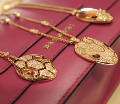 Bulgari Serpenti Seduttori pendants in rose gold with diamond pavé and gem stone eyes.