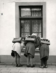 Meisjes met schooltassen / Girls with satchels   Three schoolgirls, satchels on their back, peeking through a window somewhere in Elten. The Netherlands, 1959.