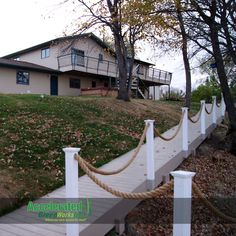 """A custom boardwalk ramp creates unique access to the beach and eliminates the need for so many steps from the house atop a hill.  Gray maintenance free decking, slender white sleeved posts and manila rope creates a maintenance-friendly system that adds to the """"lake atmosphere""""."""