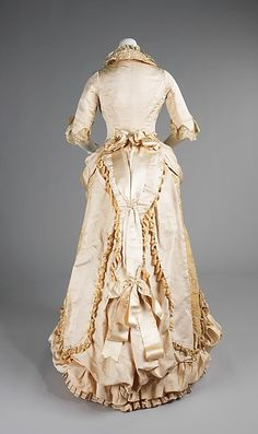 1885 American evening dress. Dressmakers from this era routinely embellish bustles with trimming, beadwork, puffs and bows to visually elevate and emphasize them.