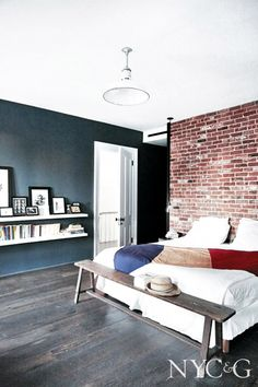 Exposed brick wall in dark bedroom with colorful throw and bookshelves