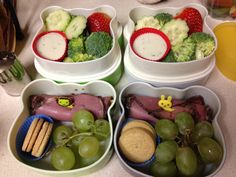 Bento with cucumber, broccoli, Ranch dressing, strawberry, meat and cheese roll, grapes, and cookies