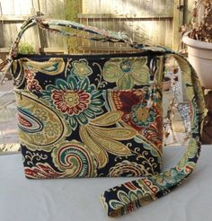 """Etsy (SewIngeniousDesigns) Tightly woven paisley/floral pattern (navy background). 10"""" W x  9"""" T  w/ a roomy 4"""" base - holds a lot!  Outer front pocket is 6.5"""" D & 8""""+ W for iPhone/small tablet. Copper lined interior w/ 7"""" zippered side pocket & 2 drop pockets on other side, w/ plenty of storage between. Fabric handle is adjustable to a 21"""" drop, w/ spring key fob & high quality nickel chrome hardware. Zipper opens full width of purse & is accented with wire beaded tassel for a little…"""