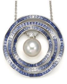 A South Sea cultured pearl, sapphire and diamond Ocean Ripple pendant with chain, Mikimoto centering a South Sea cultured pearl measuring approximately 12.9mm, accented with a round brilliant diamond and surrounded by three undulating gradated sapphire circle pendants that can be worn separately; four pendants with maker's mark for Mikimoto; estimated total sapphire weight: 9.00 carats; mounted in eighteen karat white gold.